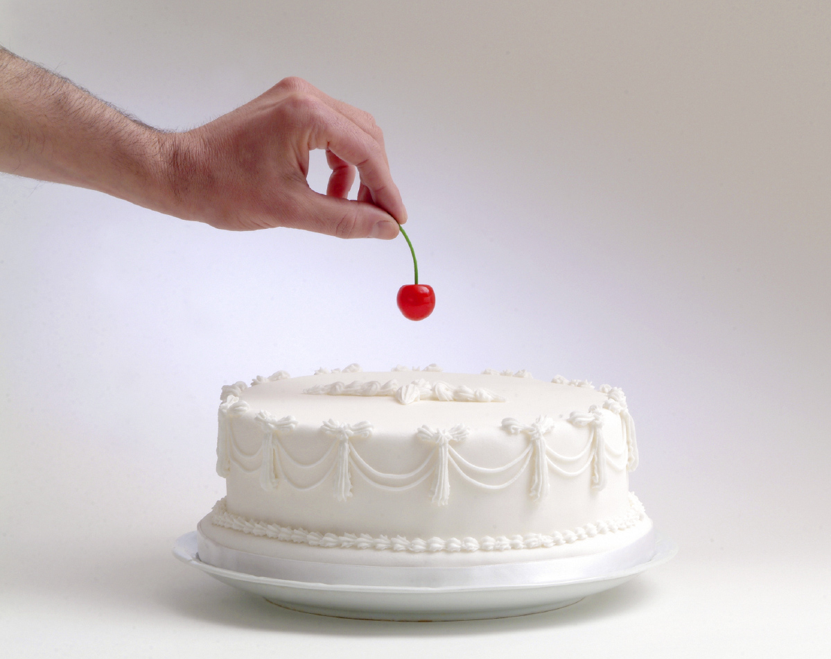 hand putting a cherry on top of a white cake