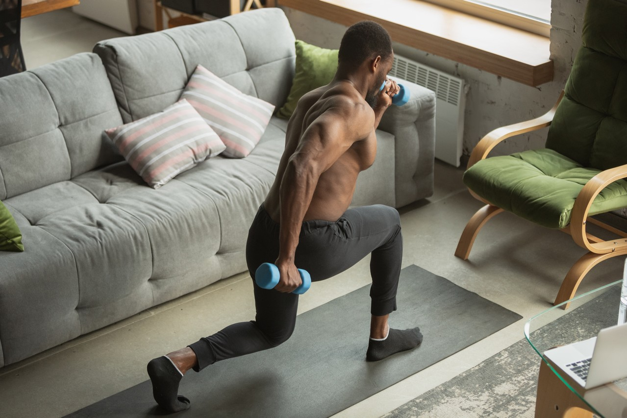 Young african-american man training at home during quarantine of coronavirus outbreak, doinc exercises of fitness, aerobic. Staying sportive during insulation. Wellness, movement concept.